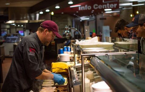UWL Chef Shawn Miller prepares a sandwich for a waiting student.