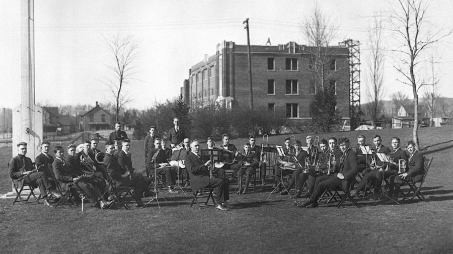 La Crosse Normal President Fassett E. Cotton, seated in the center, organized and led the school band. With many men headed to war, there weren't enough interested from the Normal School in 1918 to form a band, so Cotton recruited young men from Central High School and formed a group of about 40 musicians. Here they are posing for a practice session in the spring on the campus grounds in front of the unfinished physical education building, which was eventually named Wittich Hall. While construction started on the building in 1916, it was stopped during WWI and the building opened in 1920. The university closed in mid-October 1918 due to the Spanish flu epidemic.