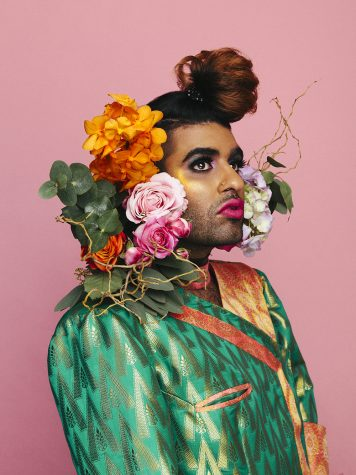Photograph of Alok Vaid-Menon in front of a pink background with flowers around their neck.