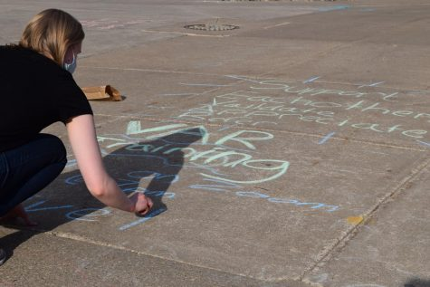 A photo of a student writing with chalk on campus.