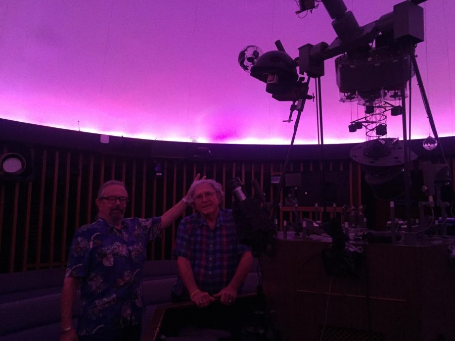Tom Thompson and Robert Allen stand in the UWL Planetarium next to projectors under a pink sky image.