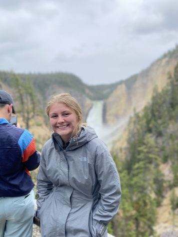 Julia Van Fleet smiling with a view of a waterfall in the background.